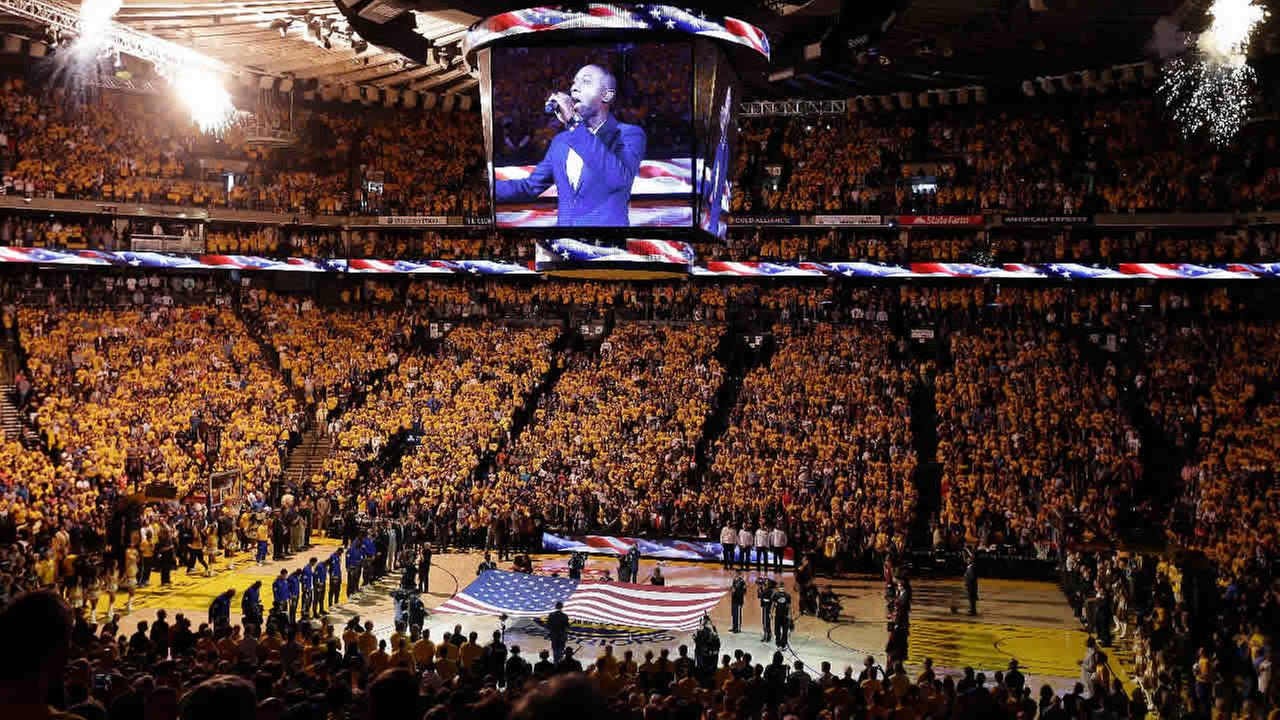 Fans at Oracle Arena watch as musician Aloe Blacc performs the national anthem before Game 7 of basketballs NBA Finals between the Golden State Warriors and the Cleveland Cavaliers in Oakland, Calif., Sunday, June 19, 2016.