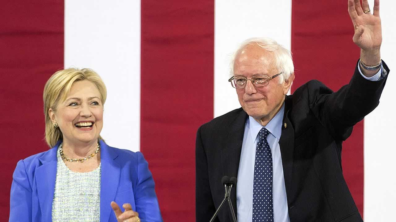 Democratic presidential candidate Hillary Clinton smiles as she arrives on stage with Sen. Bernie Sanders, I-Vt., Tuesday, July 12, 2016, in Portsmouth, N.H.