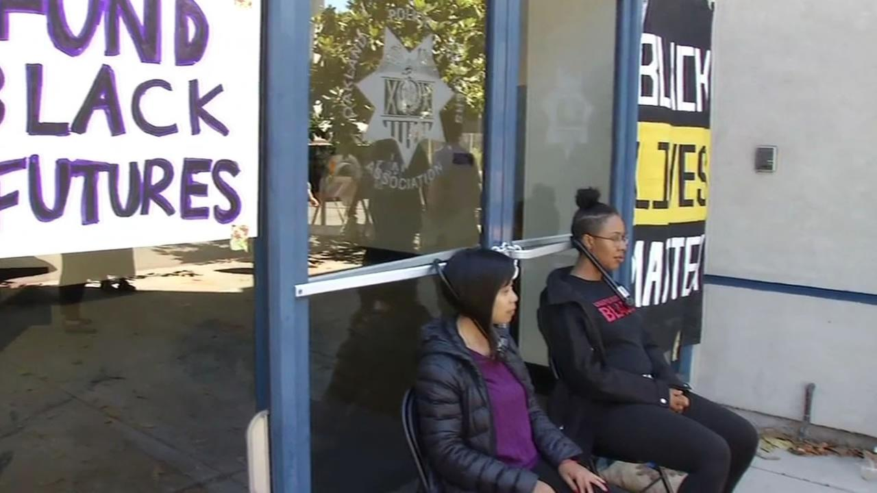 This image shows protesters locked to the Oakland Police Officers Association building in Oakland, Calif. on July 20, 2016.