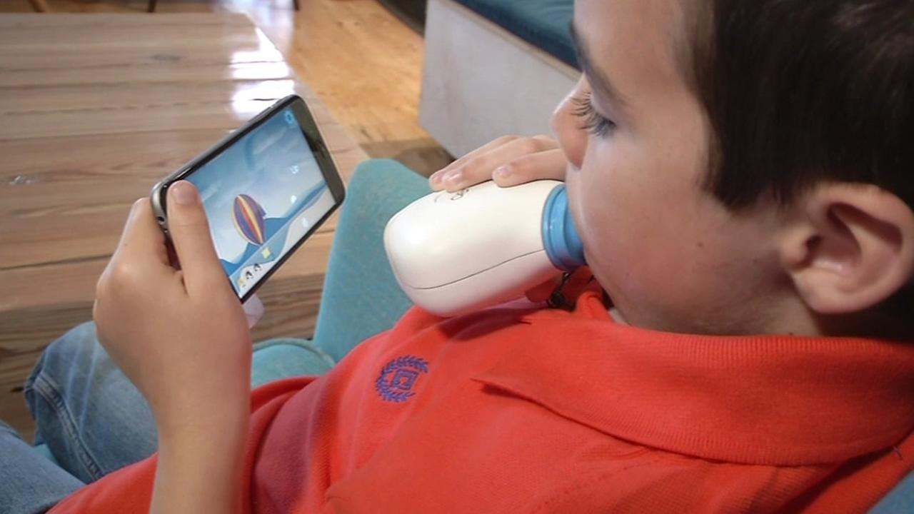 This image shows eight year old Finn Seybold using a mini spirometer, created by a Bay Area startup, called a Aeris.