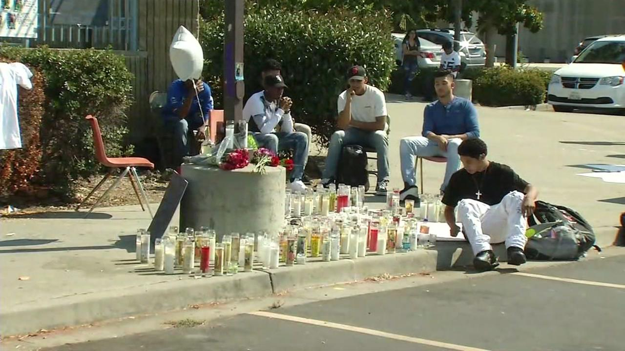 James Logan High School sit by memorial for students killed in car crash, Tuesday, September 6, 2016.