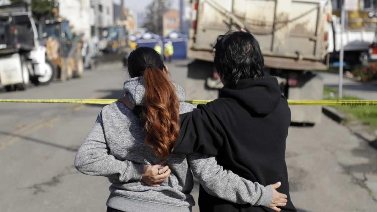 Two women watch the scene of a warehouse fire, Sunday, Dec. 4, 2016, in Oakland, Calif.