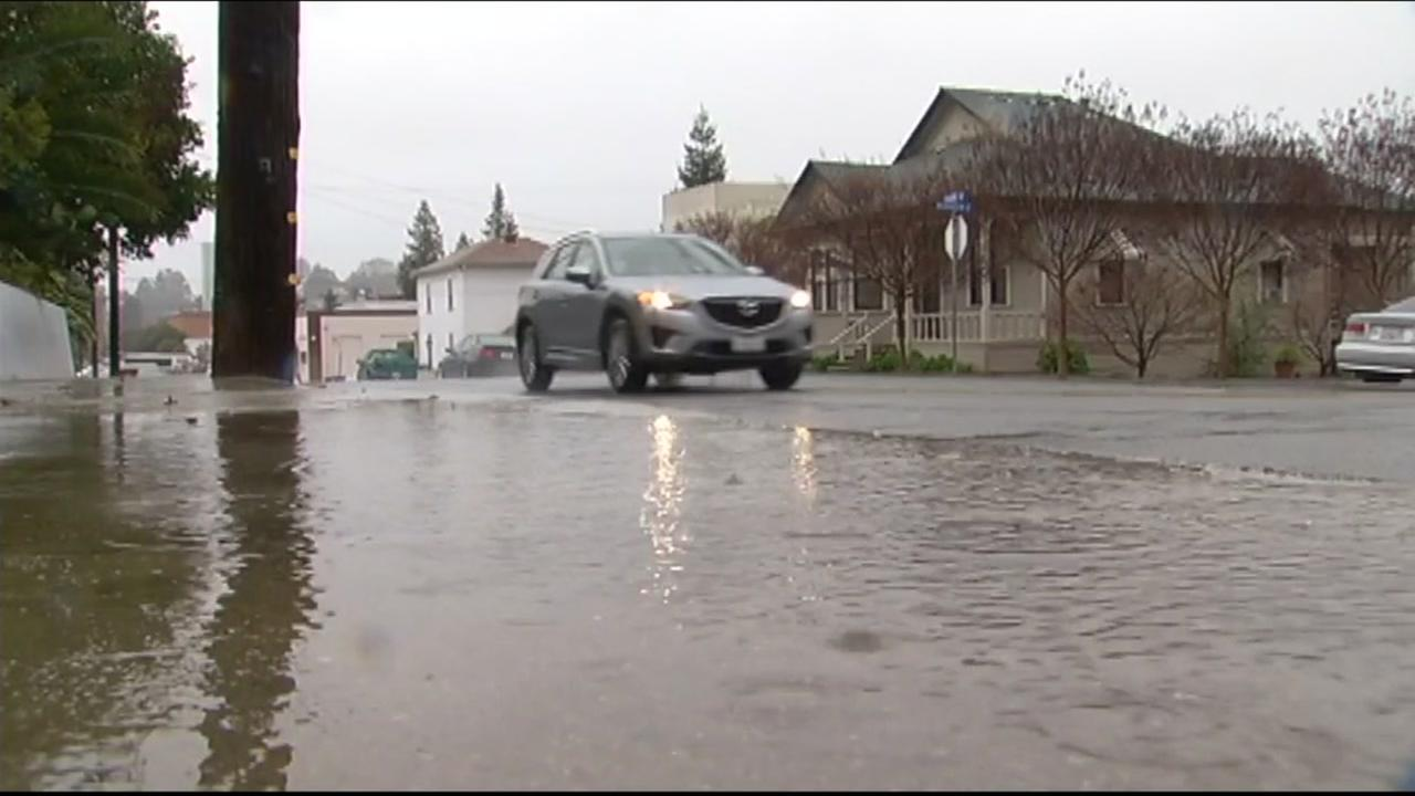 FILE -- car goes through flooded street