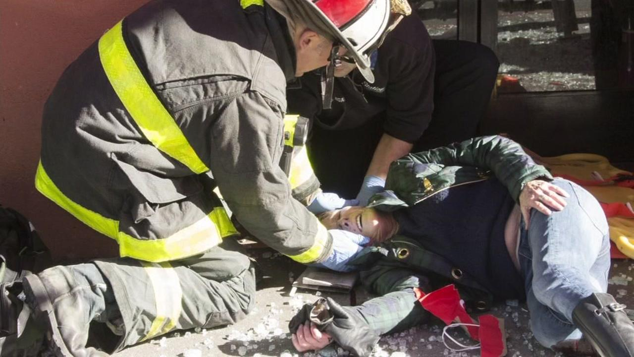 First responders tend to a woman injured after a car crashed into a bus stop in San Franciscos Chinatown neighborhood on Dec. 16, 2016.