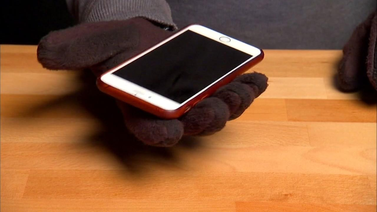 A person wearing texting gloves is seen holding a smartphone in this undated image.
