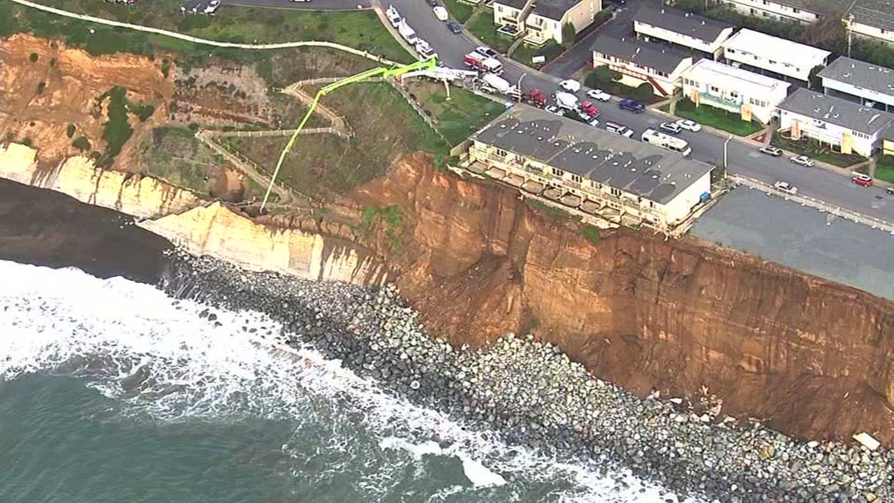 Aerial footage shows an apartment building in Pacifica eroding into the sea.