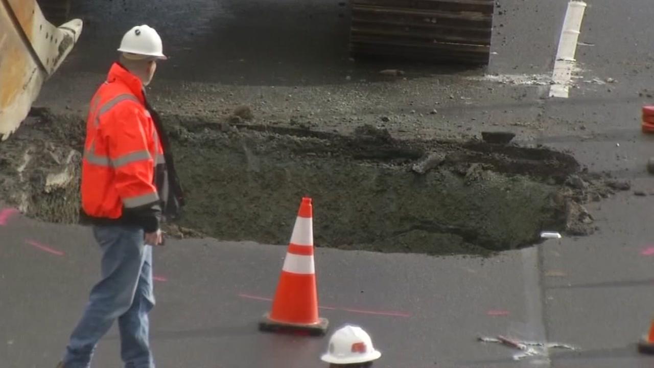 A worker walks near a sinkhole on Highway 13 in Oakland, Calif. on Jan, 23, 2017.