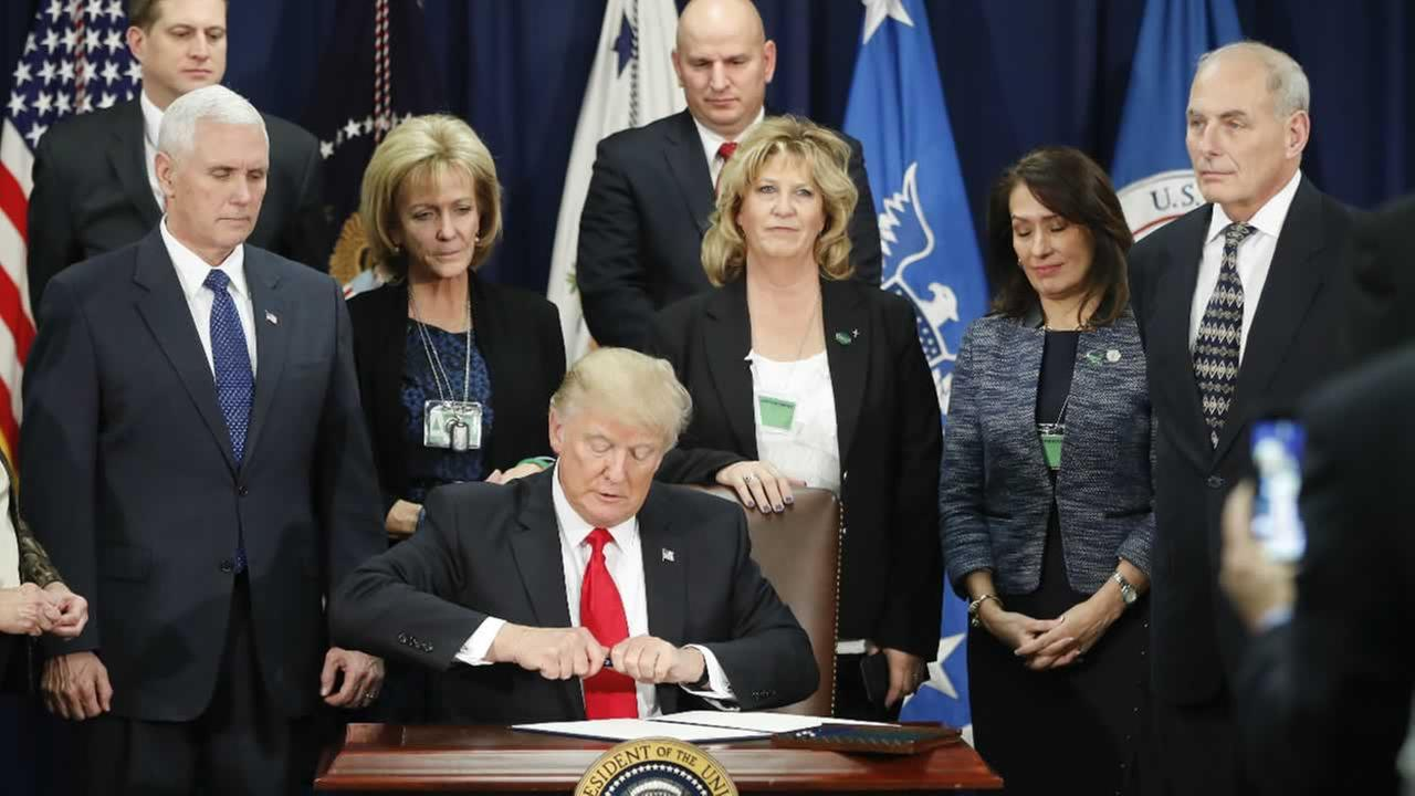 President Donald Trump takes the cap off a pen before signing an executive order during a visit to the Homeland Security Department HQ in Washington, Wednesday, Jan. 25, 2017.