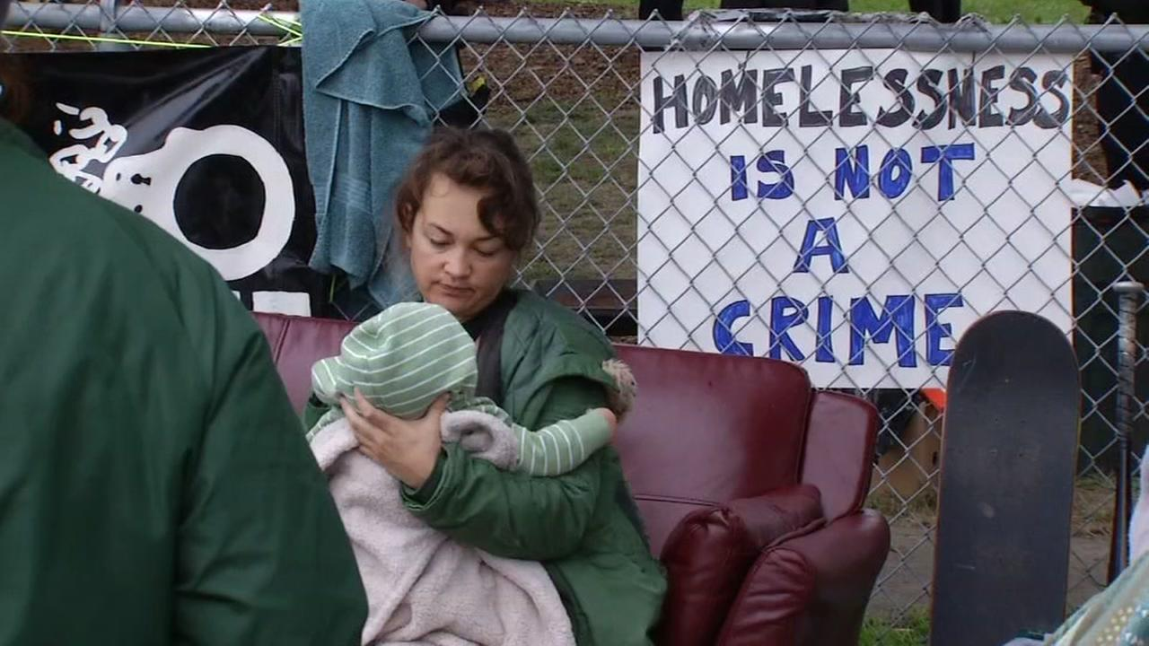 A woman holds a baby at a homeless village in Oakland, Calif. on Thursday, February 2, 2017.