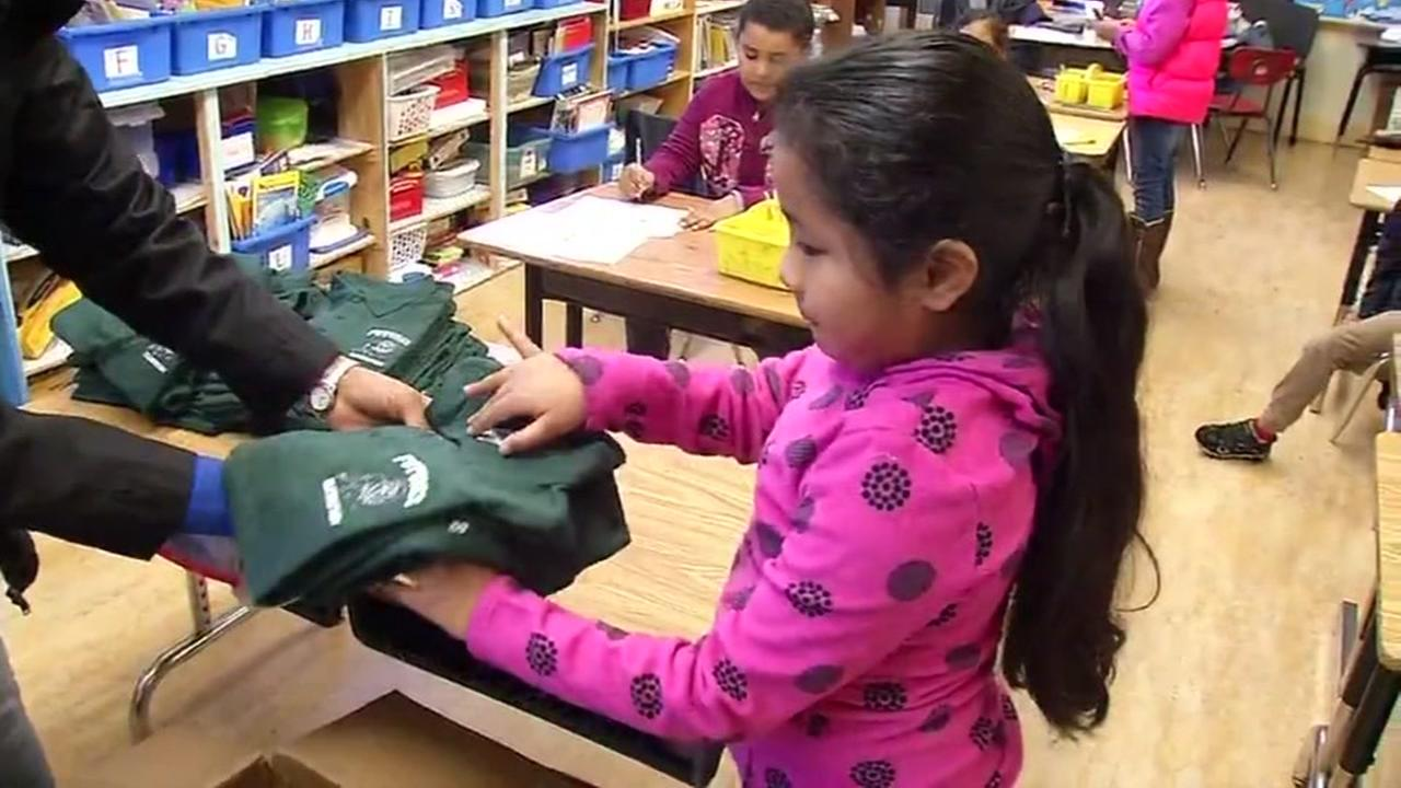 A young girl is seen receiving a free shirt at Futures Elementary School in Oakland, Calif. on Friday, February 3, 2017.