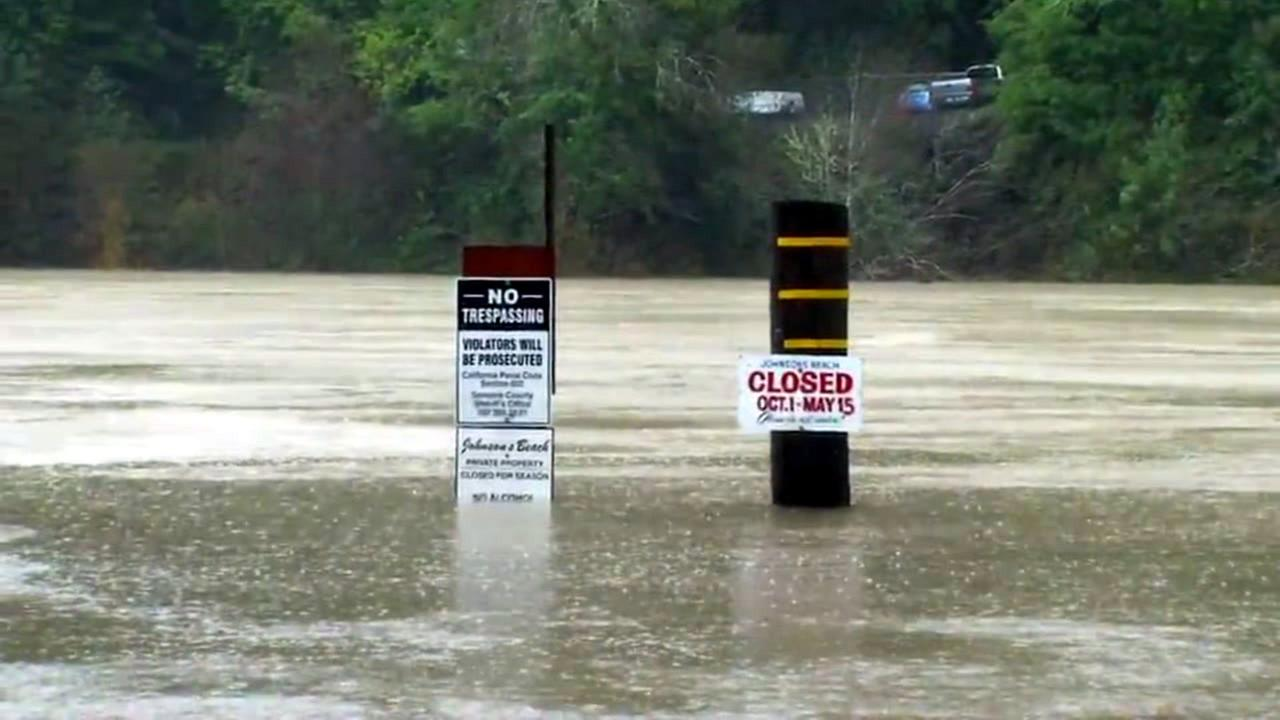 Warning signs are posted in the Russian River in Guerneville, Calif. on Thursday, February 9, 2017.