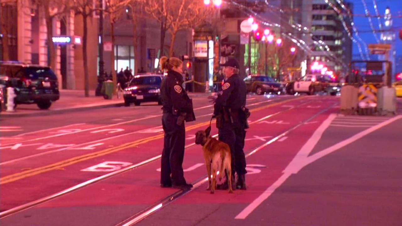 San Francisco police officials and a bomb-sniffing dog stand on Market Street during an evacuation of the Anti-Defamation Leagues office on Feb. 27, 2017.