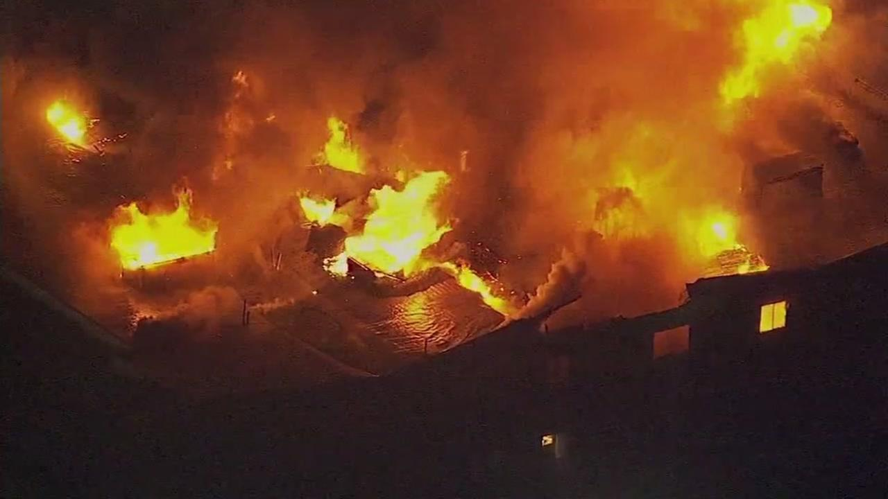 This is an image of flames shooting out of the roof of the apartment complex in West Oakland, Calif. on Monday, March 27, 2017 that left four people dead.