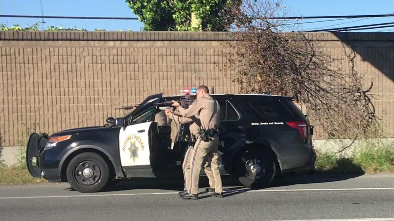 CHP officers stand with their guns drawn in San Mateo, Calif. on Friday, April 28, 2017.