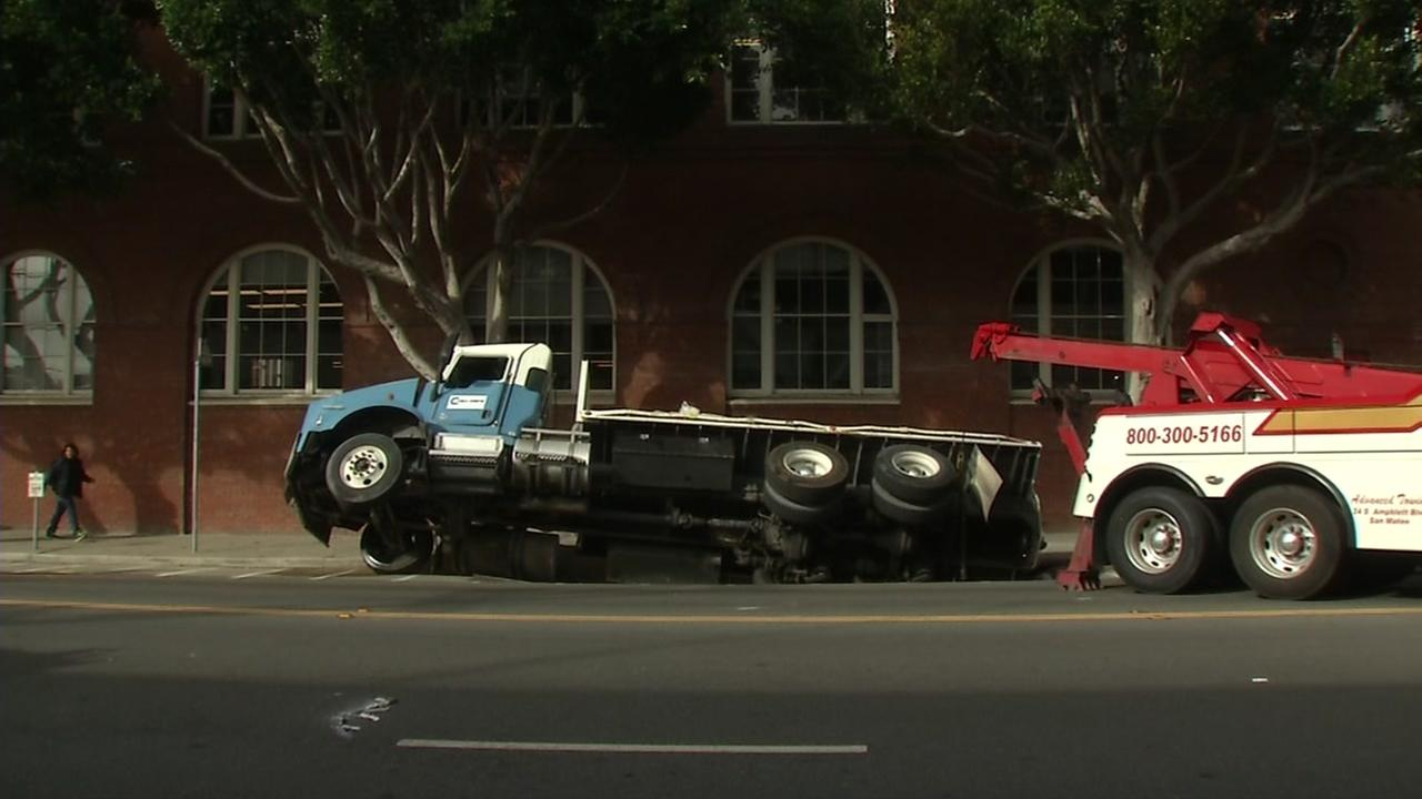 A flatbed truck is seen after nearly being swallowed by a sinkhole on 7th Street in San Francisco on Friday, May 5, 2017.