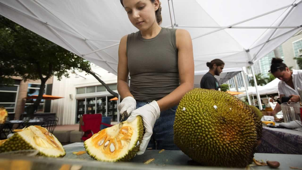 Sara Diaz, from LNB Groves, cuts a jackfruit at the Monday night green market in downtown Miami, Monday, June 8, 2015.
