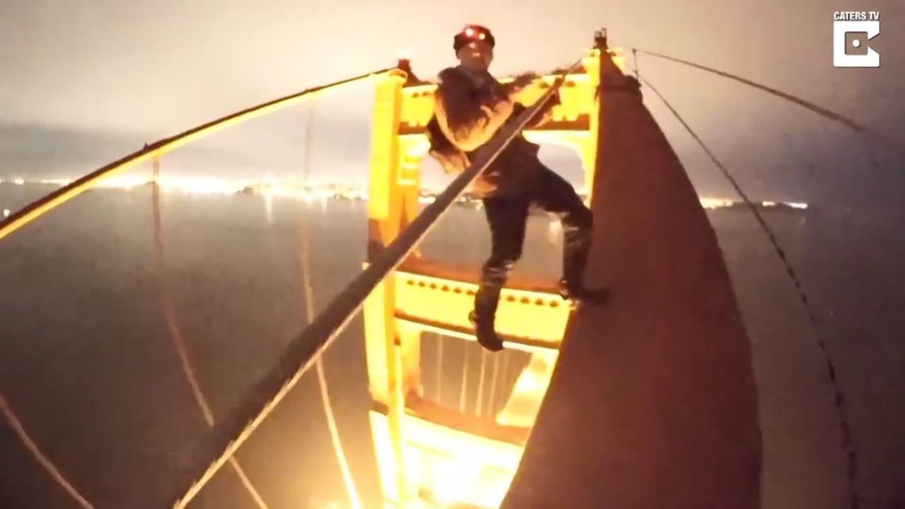 Teens climb the Golden Gate Bridge in this undated image.
