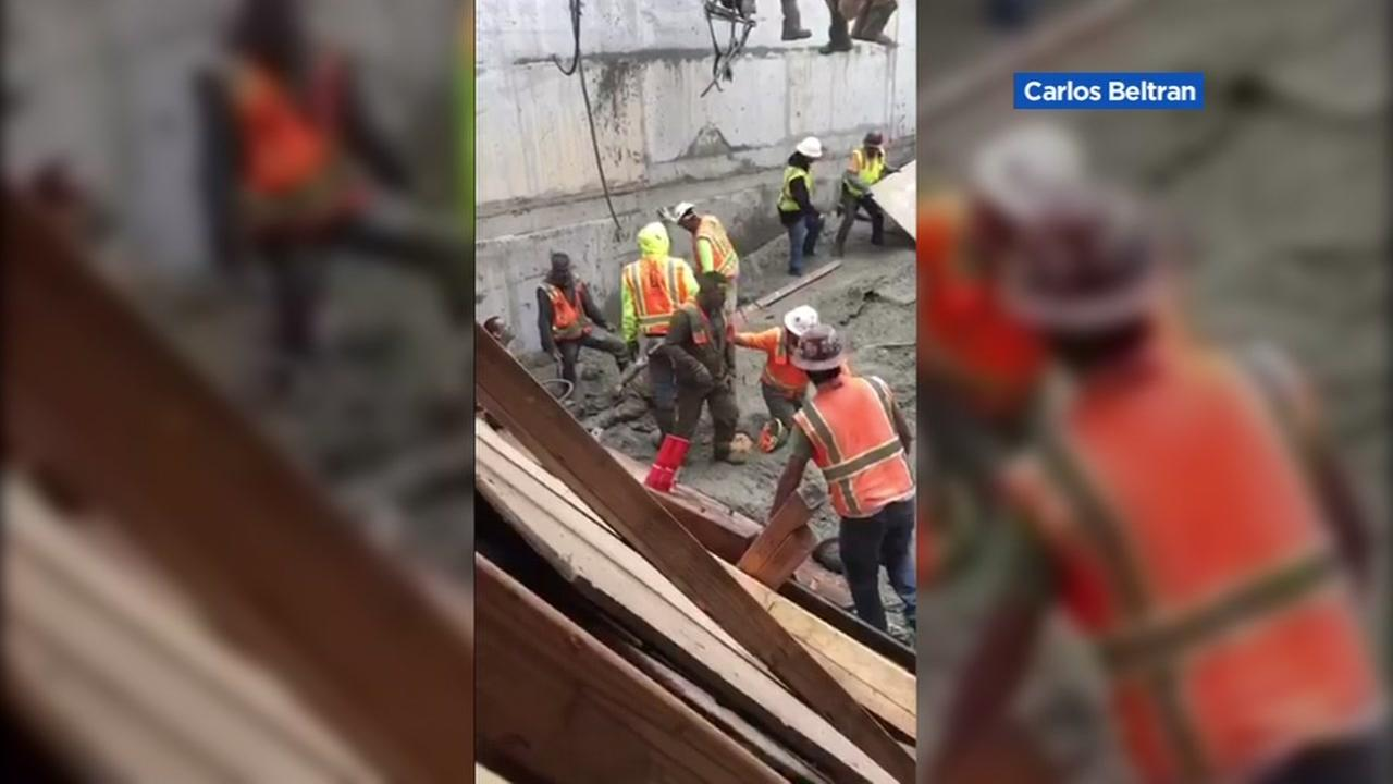 Construction workers are seen in Oakland, Calif. at a building that partially collapsed on Friday, May 26, 2017.