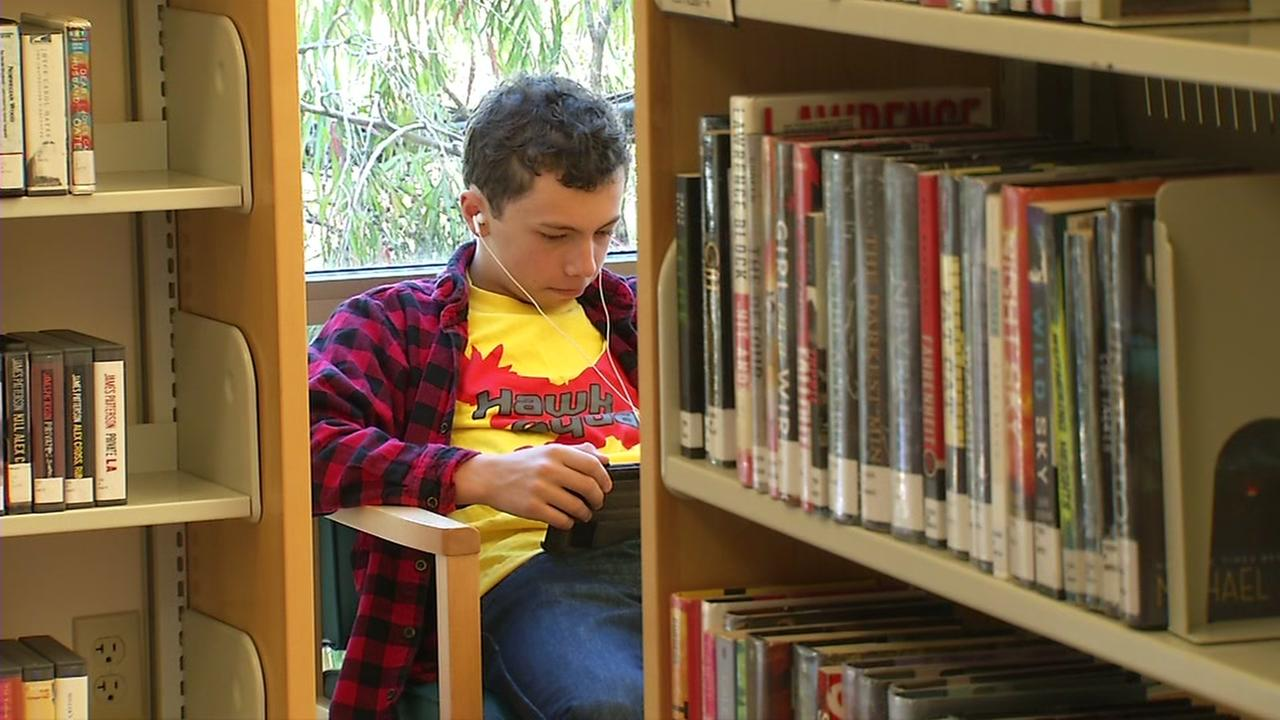 A person is seen reading a book in a public library in San Francisco in this undated image.