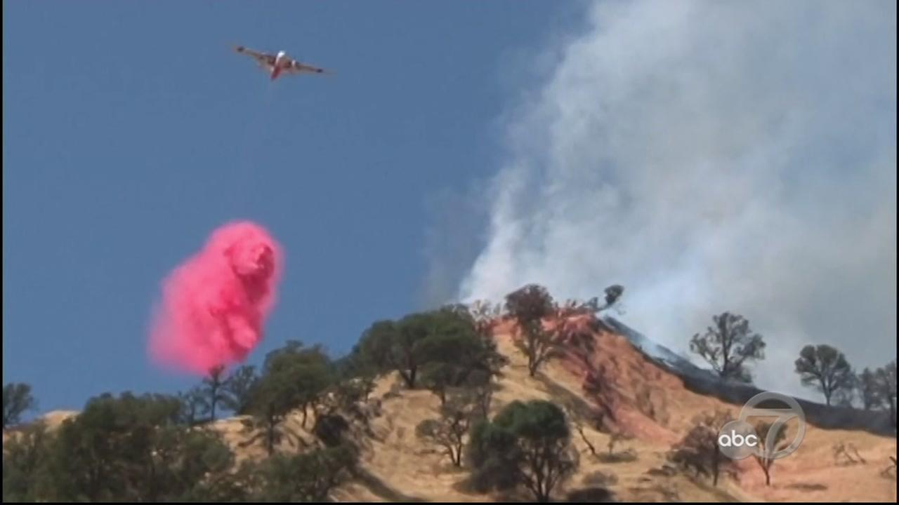 A firefighting airplane drops fire retardant on a growing grass fire in Yolo County, Calif. on Thursday, June 6, 2017.