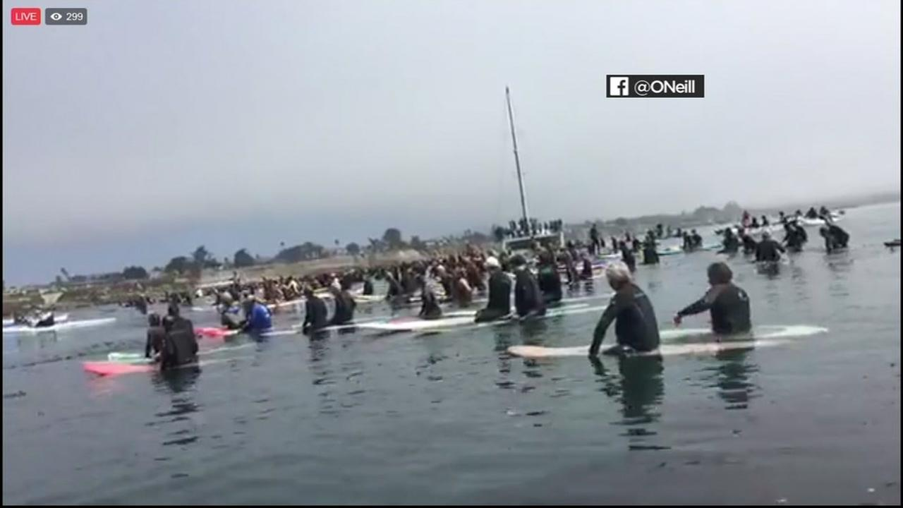 Surfers are seen paddling out to honor Jack ONeill near the Santa Cruz coastline on Sunday, July 9, 2017.