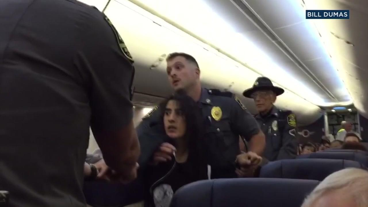A woman is seen with officers on a Southwest flight in this undated image.