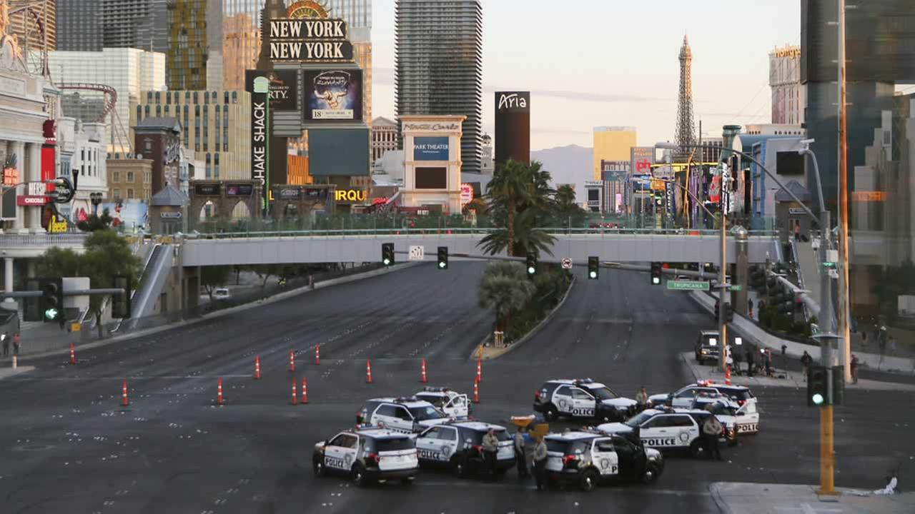 A roadblock is shown through a gap in a glass partition at the corner of Las Vegas Boulevard and Tropicana Avenue, Monday, Oct. 2, 2017, in Las Vegas.