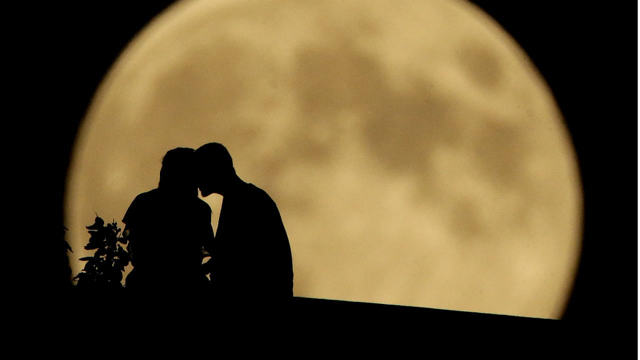 A couple sits on a bluff overlooking the Missouri River as the full moon rises in the distance Monday, Sept. 8, 2014, in Kansas City, Mo. (AP Photo/Charlie Riedel)