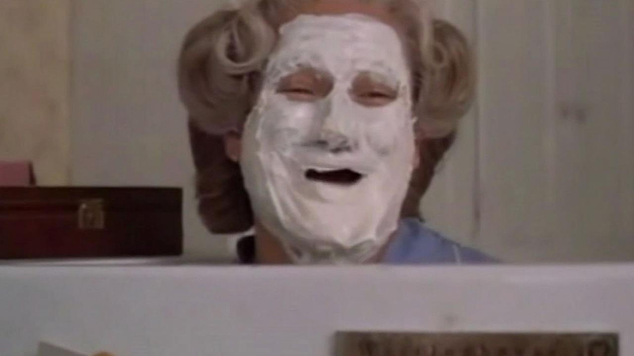 Robin Williams as the character Mrs. Doubtfire with cake on his face