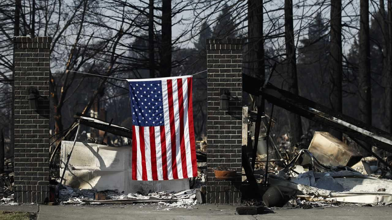 An American flag hangs on a burned home, Sunday, Oct. 15, 2017, in the Coffey Park neighborhood in Santa Rosa, Calif., that was devastated by a wildfire.