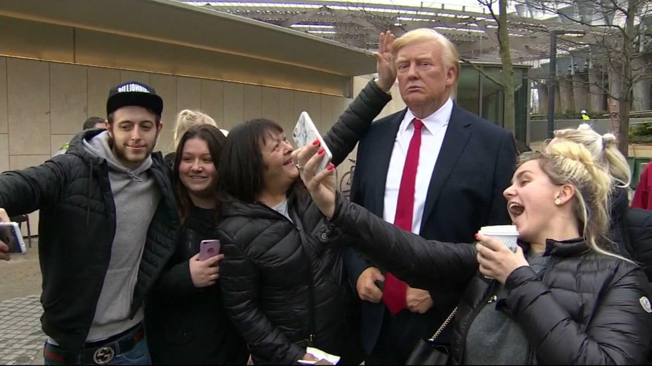 A group of people post for a picture with a wax figure of President Donald Trump outside of the U.S. embassy in London on Friday, Jan. 12, 2018.