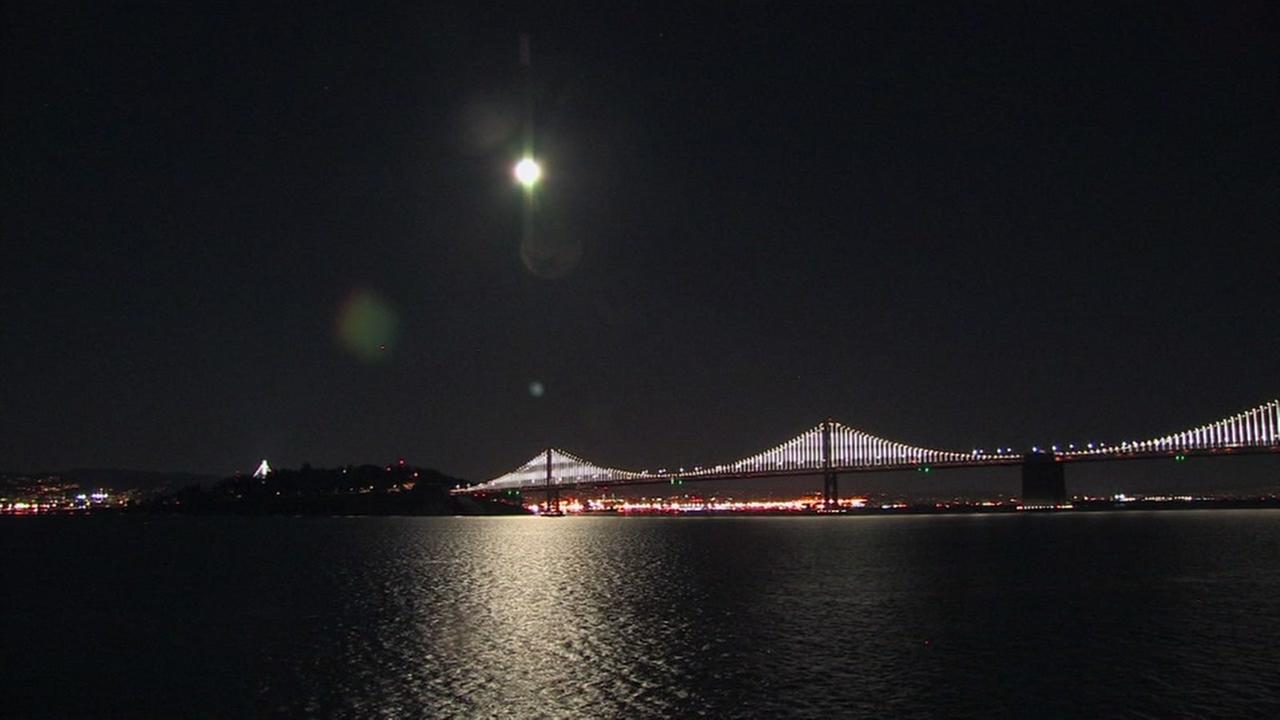 This is an undated image of the moon rising over the Bay Bridge.