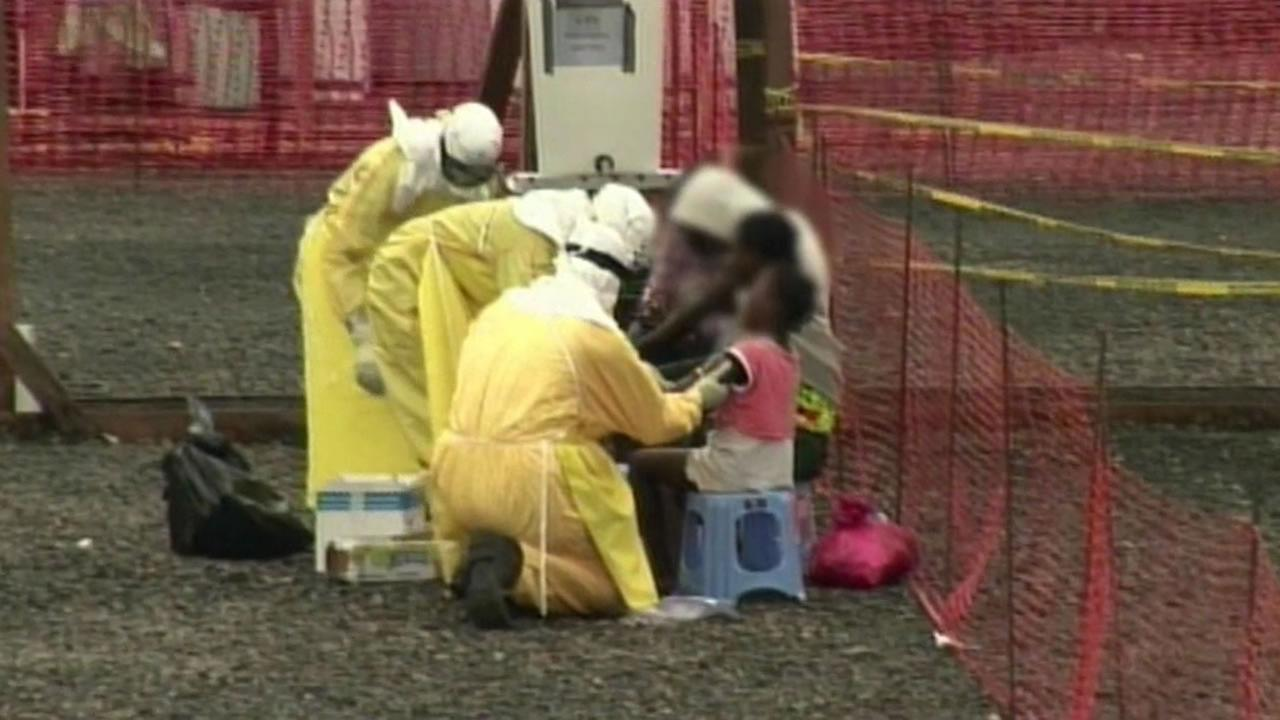 Doctors assisting patient with Ebola in West Africa