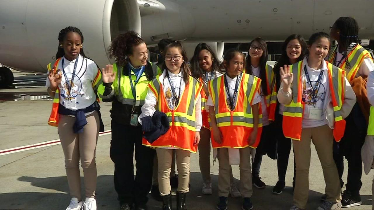 Oakland middle school students pose in front of a United airplane on Thursday, March 1, 2018.