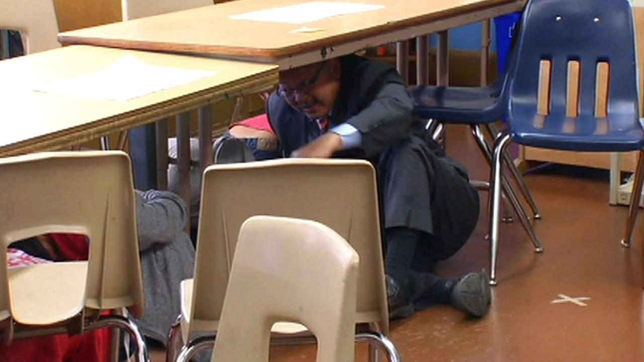San Francisco Mayor Ed Lee took cover under a school desk as part of the Great California ShakeOut earthquake drill.