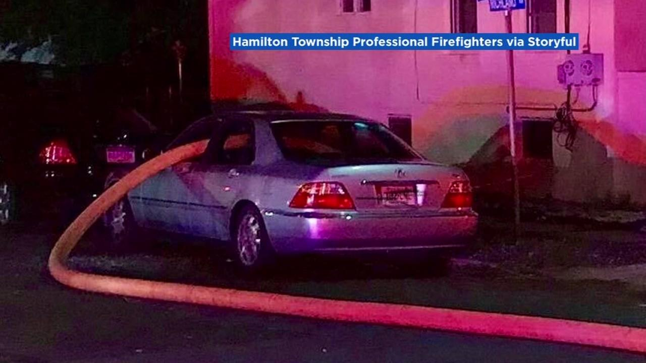A fire hose is seen through a car window after a car parked in front of a hydrant in Hamilton Township, New Jersey in this undated image.
