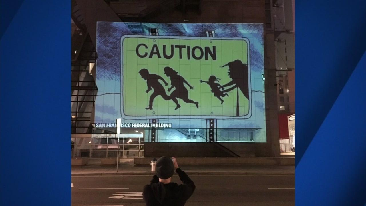 A political cartoon is seen projected on a San Francisco building on Monday, June 19, 2018.