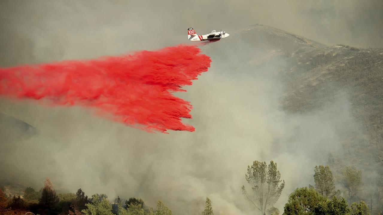 An air tanker drops retardant on a wildfire burning above the Spring Lakes community on Sunday, June 24, 2018, near Clearlake Oaks, Calif.