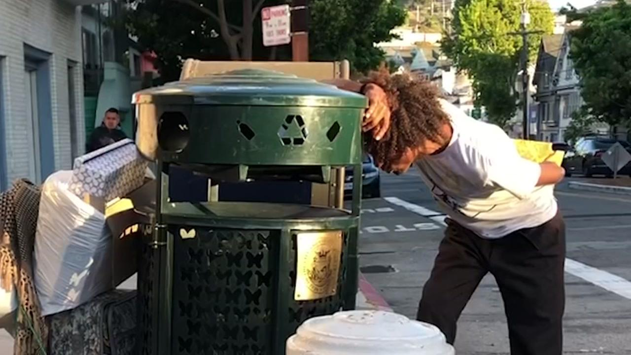 This undated image shows a homeless person looking through a garbage can in San Francisco.