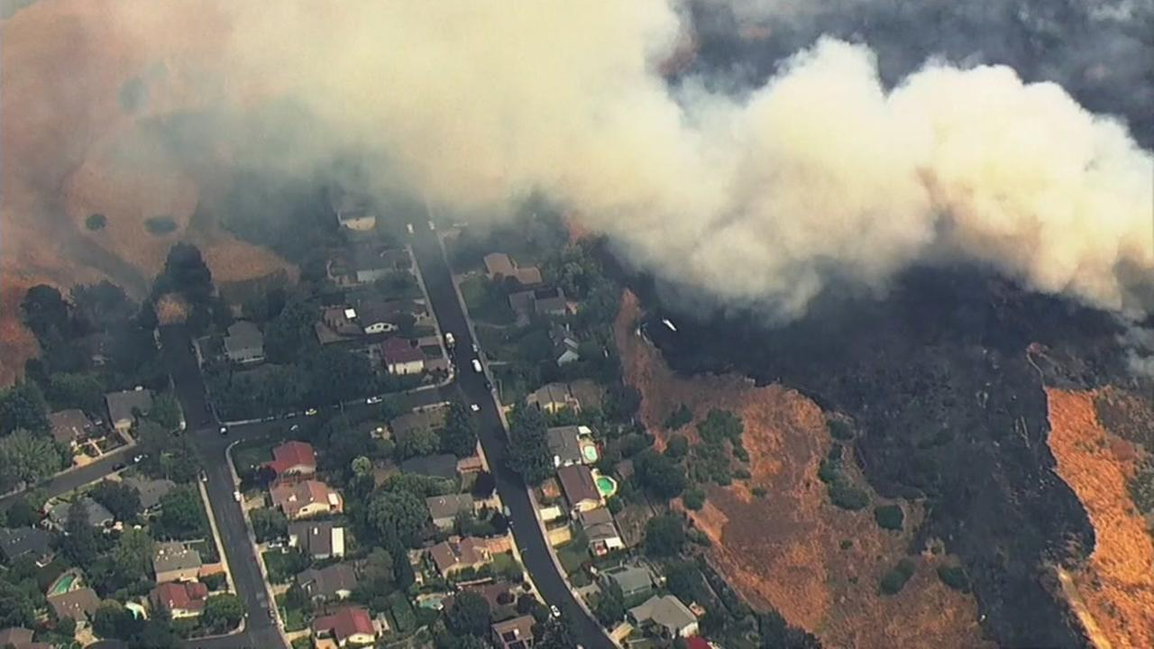 A fire burns dangerously close to homes in Moraga, Calif. on Monday, July 2, 2018.