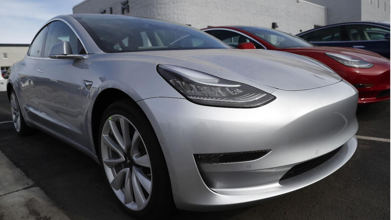In this April 15, 2018, photograph, unsold 2018 Model 3 Long Range versions sit on a Tesla dealers lot in the south Denver suburb of Littleton, Colo. (AP Photo/David Zalubowski)
