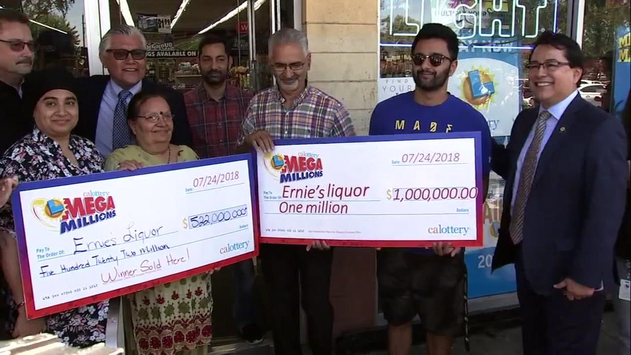 The owner of Ernies Liquor in San Jose holds his million dollar check after selling the Mega Millions jackpot winning ticket on Wednesday, July 25, 2018.