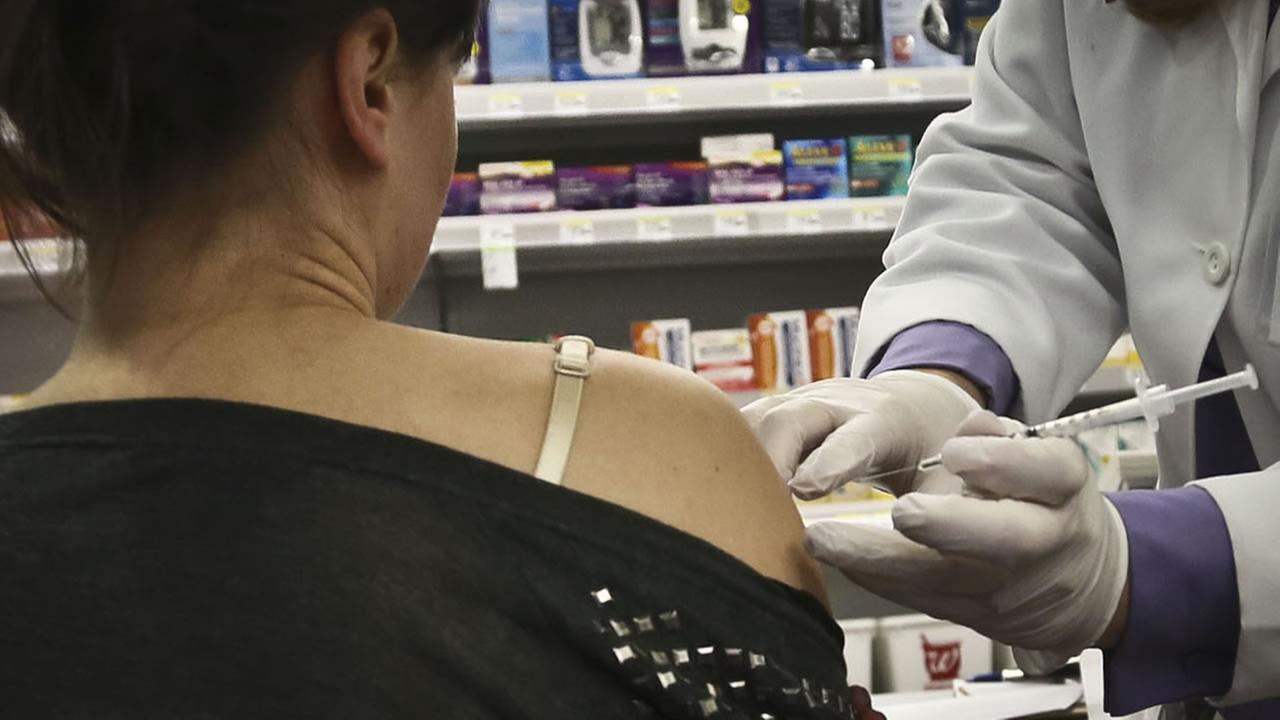 Pharmacist Stacia Woodcock, a pharmacy manager for Walgreens in New New York, administer a flu vaccine on site, Monday, Jan. 14, 2013. (AP Photo/Bebeto Matthews)