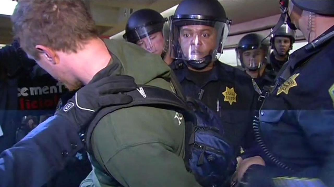 Police arrest a protester during a BART demonstration Friday morning.