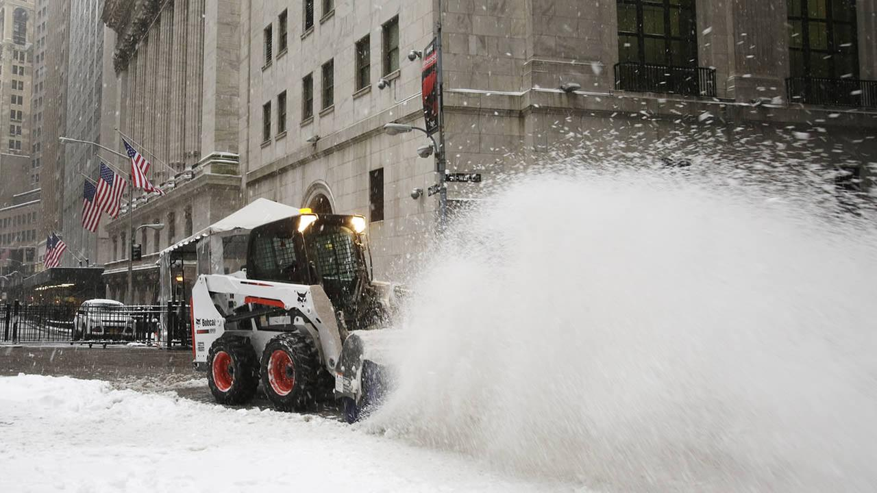 A plow clears snow from Wall Street in front of the New York Stock Exchange, Tuesday, Jan. 27, 2015. (AP Photo/Mark Lennihan)