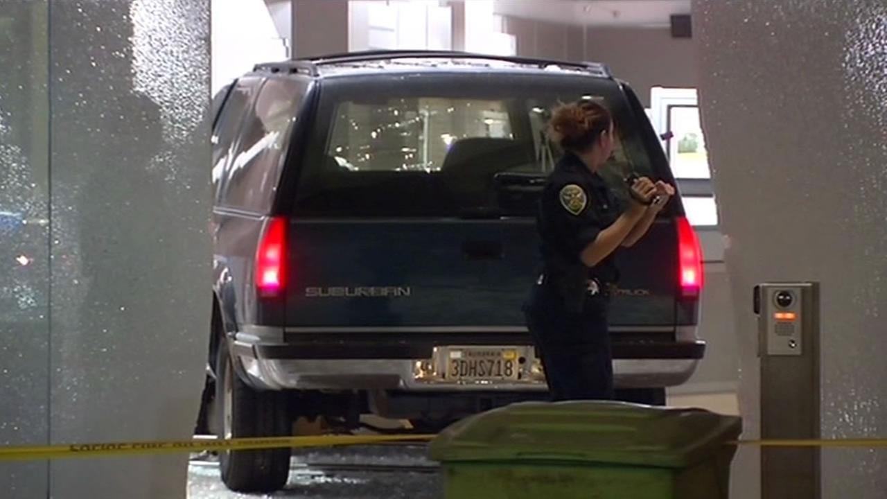Police comb the scene where three armed men rammed a stolen SUV into the Wells Fargo History Museum in San Francisco and took gold nuggets from a display case.