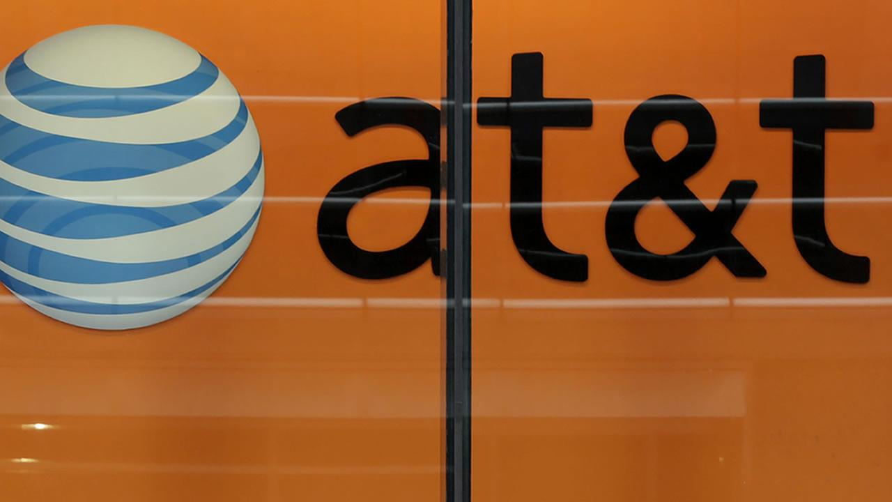 In this Tuesday, Oct. 21, 2014 photo, people pass an AT&T store on New Yorks Madison Avenue.(AP Photo/Richard Drew)