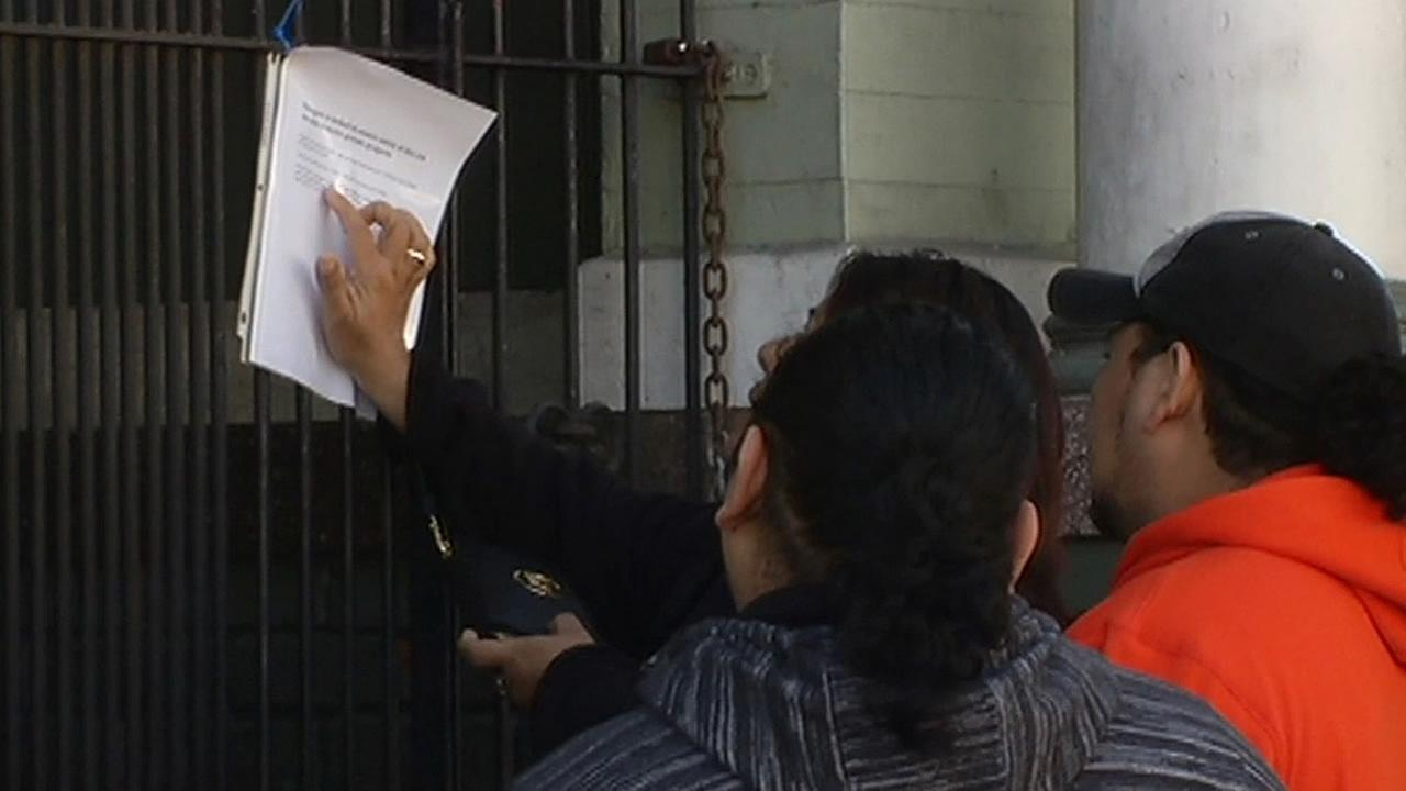 tenants read note outside locked gates of their home