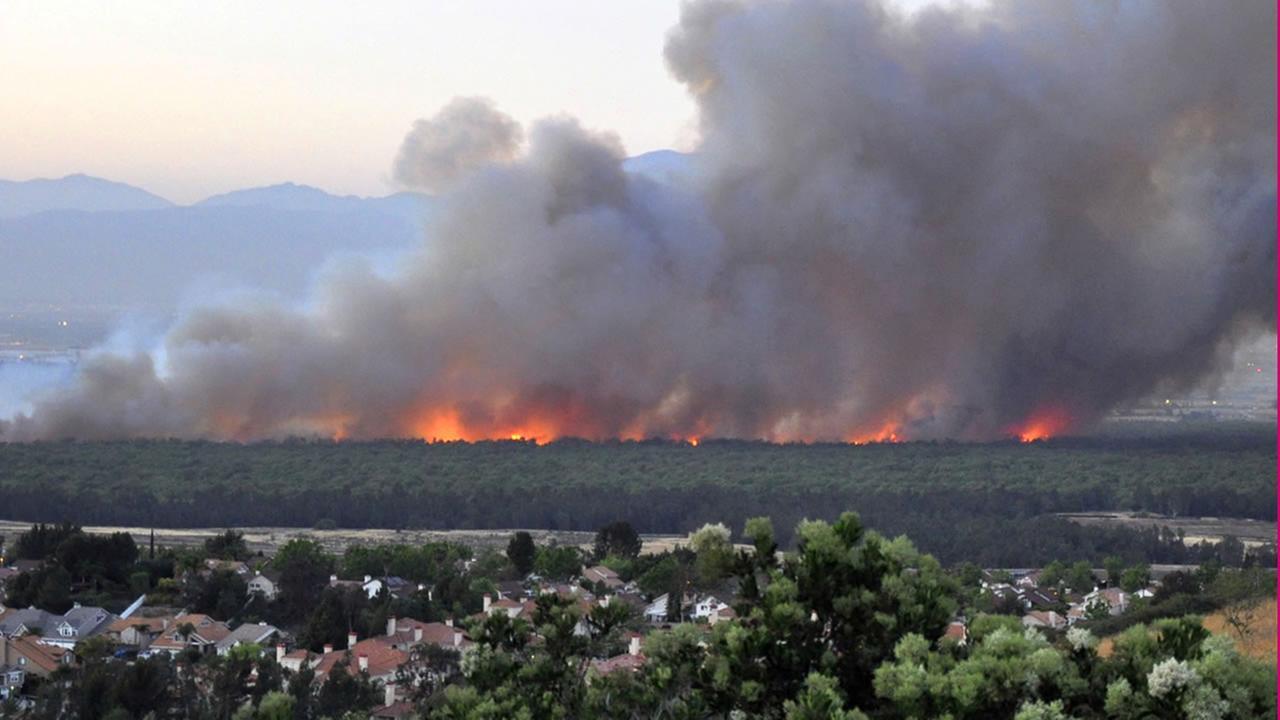 In this Saturday, April 18, 2015 photo provided by Daniel Cole, flames burn in the Prado Dam Flood Control Basin in Southern California. (Daniel Cole via AP)
