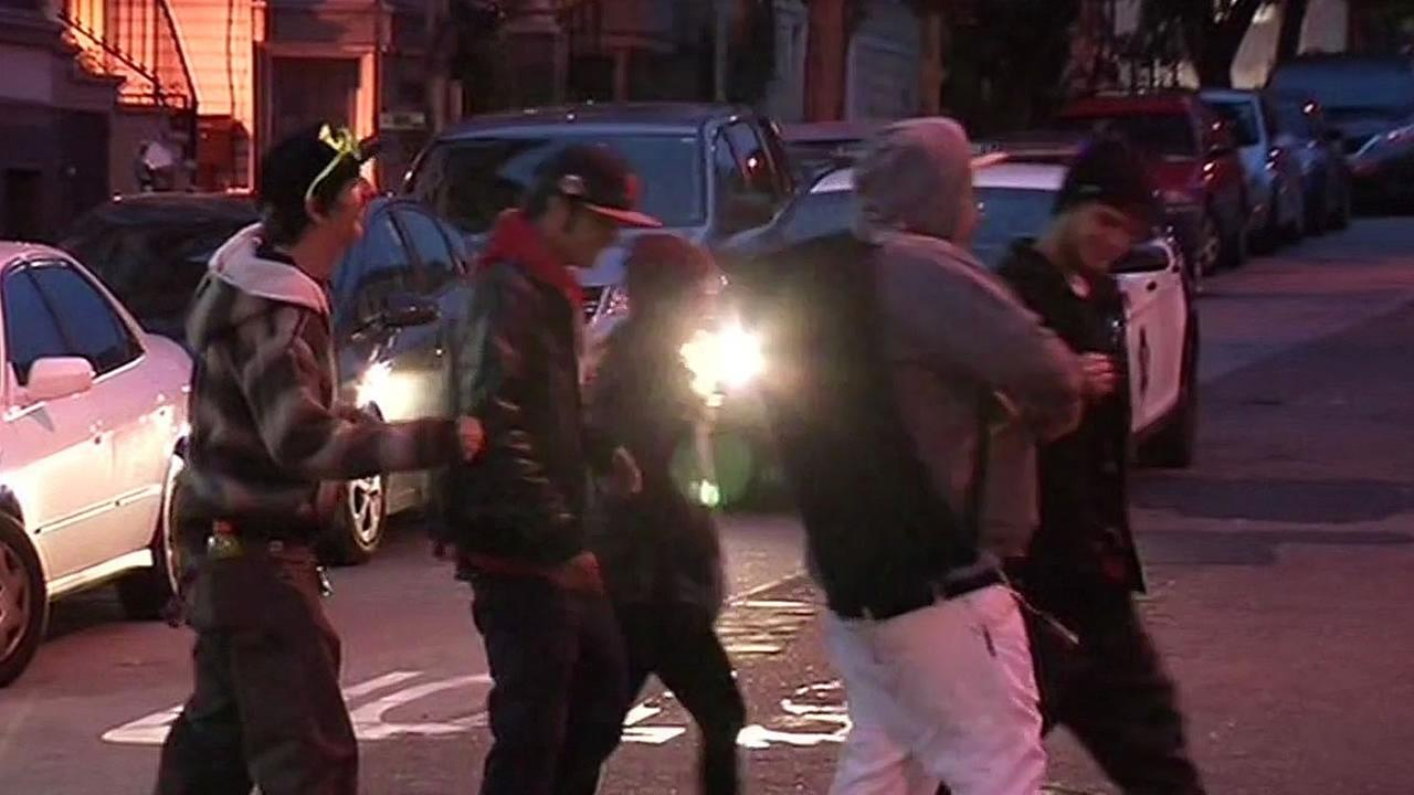 group of people cross a cop car on Haight Street